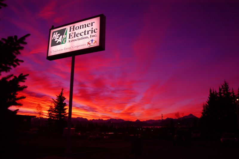 Homer Electric Cooperative lit signage in front of a bright purple, pink, orange, and yellow sunrise