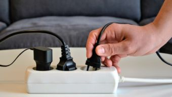 Three different electrical plugs connected to a power strip or extension block. Electric plugs with Multi-socket power strip, panoramic view. Male hand connecting an electrical plug to a power strip