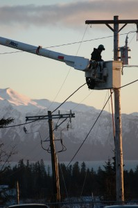 Homer Electric Lineman in the bucket of a boom truck working on a power line with mountains in the distance