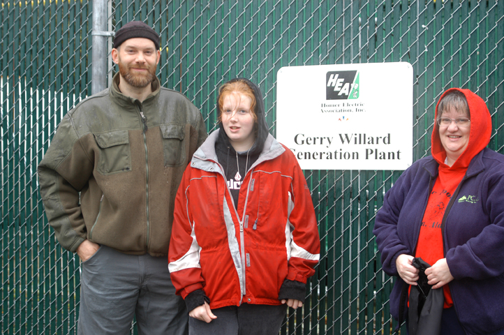 Three people standing in front of a gate with a sign, Gerry Willard Generation Plant
