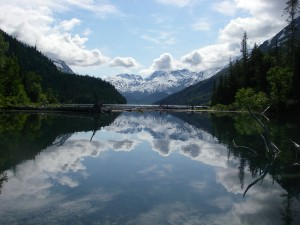 Lake with the sky reflected on it, surrounded by forests and mountains
