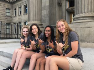 young girls doing the hang ten hand gesture, sitting on steps in front of a building,