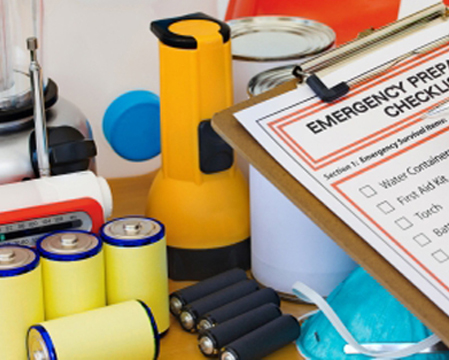 Emergency preparedness list on a clipboard, with a flashlight, batteries and other supplies on a table